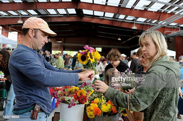 September 25, 2010 Shirley Moody buys flowers from Tim Noxon of Vicki's Veggies of Prince Edward County at the opening of the Evergreen Brickworks.