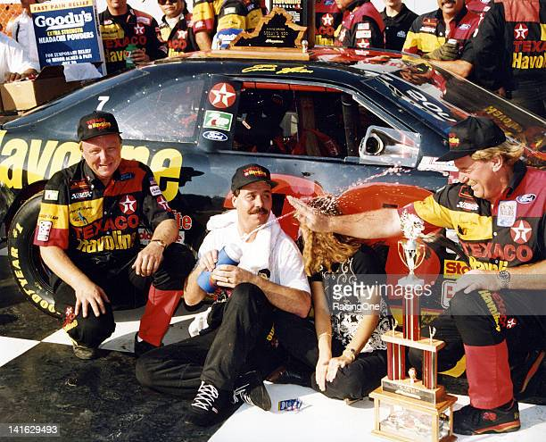 Driver Ernie Irvan sprays car owner Robert Yates with water as crew chief Larry McReynolds looks on while they celebrate in victory lane at...