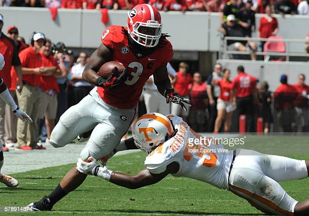 Todd Gurley Georgia Bulldogs running back rushes for yardage as Jalen Reeves-Maybin Tennessee Volunteers linebacker attempts to make the tackle...
