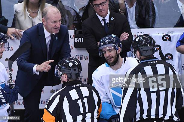 Team Europe head coach Ralph Krueger debates a penalty call with referee Kelly Sutherland and linesman Pierre Racist during the first WCOH best of...