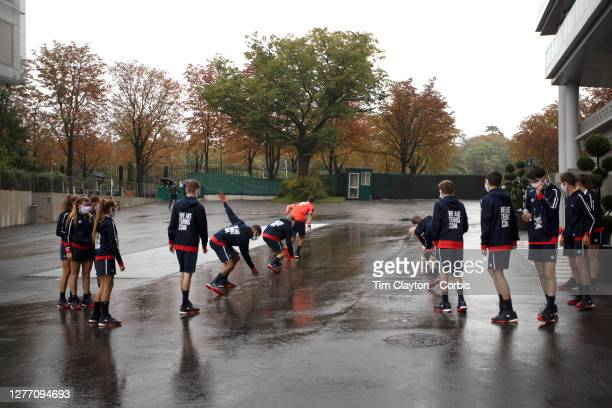 September 28. Ball boys and ball girls warming up outside Court Philippe-Chatrier on a wet autumn day in preparation for day two of of the French...