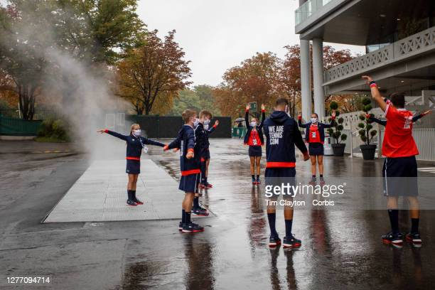 September 28. Ball boys and ball girls warming up outside Court Philippe-Chatrier on a wet autumn day as steam rises from a vent as they prepare for...