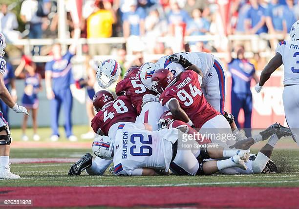 Louisiana Tech Bulldogs quarterback J'mar Smith's helmet flies in the air during a sack by Arkansas Razorbacks defensive lineman Deatrich Wise Jr...