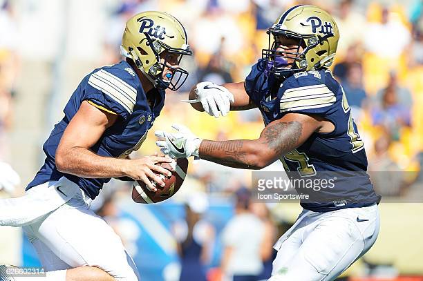 Pittsburgh Panthers quarterback Nathan Peterman makes a fake handoff to running back James Conner during a NCAA football game between the Pittsburgh...