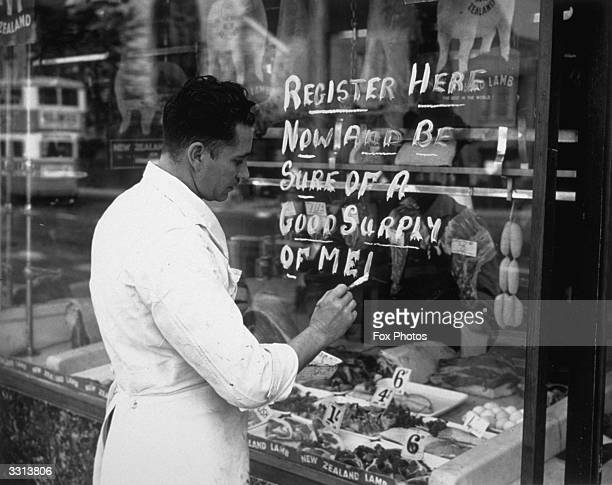 A butcher painting a meat registration notice on the window of his shop 'Register Here Now And Be Sure Of A Good Supply Of Meat'