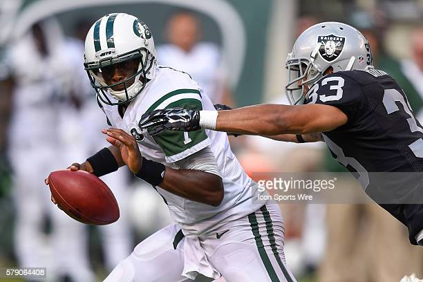 New York Jets quarterback Geno Smith is chased by Oakland Raiders strong safety Tyvon Branch during the second half of a NFL matchup between the...
