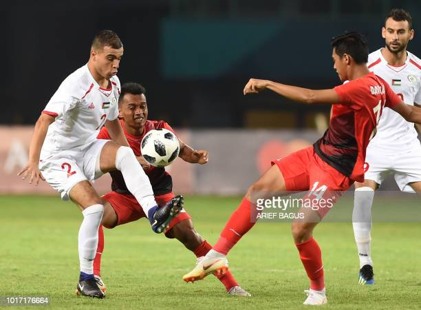 Septian David Maulana of Indonesia tussles for the ball with Ahmed Qatmish of Palestine during the 18th Asian Games football match at the Patriot...