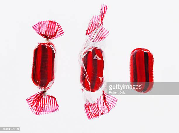 sequence of hard candy being unwrapped - candy wrapper stock photos and pictures