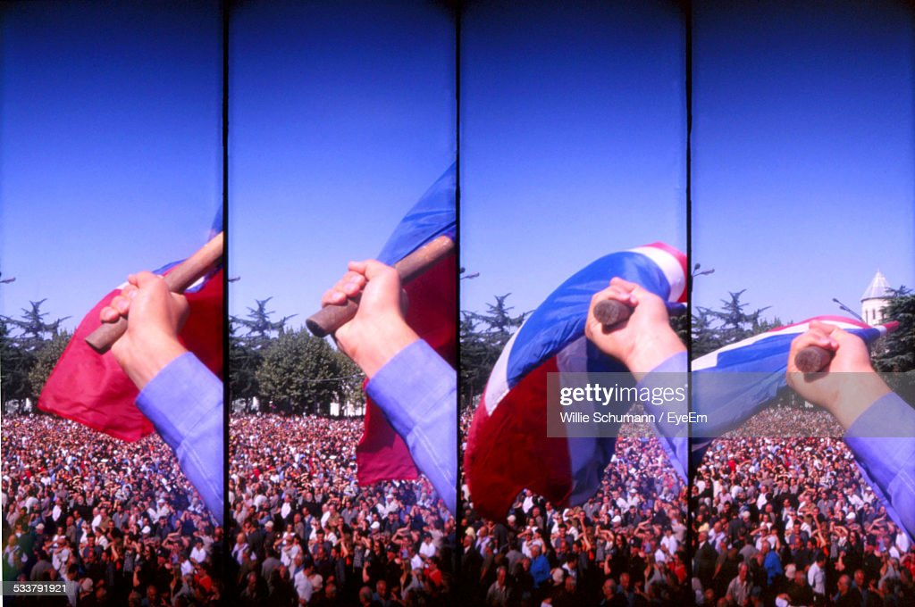 Sequential Series Of Four Images Combined, Human Hand With Flag And Crowd In Background : Foto stock