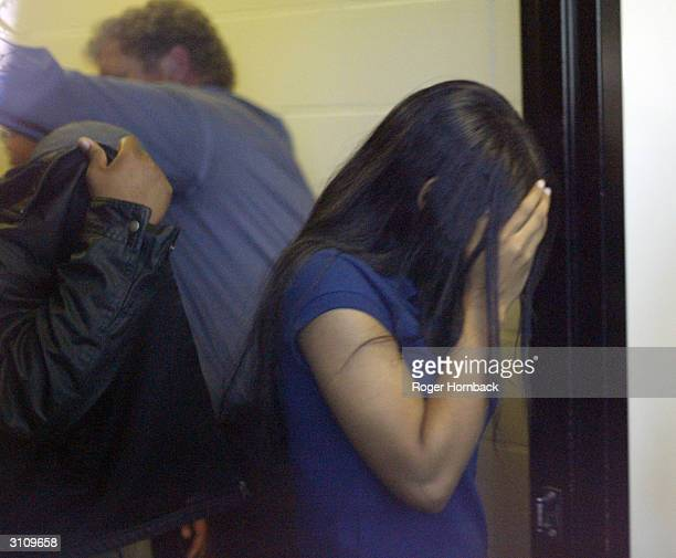 Serafino Wesson the son of Marcus Wesson and an unidentified girl shield their faces from the media March 18 2004 in Fresno California while on their...