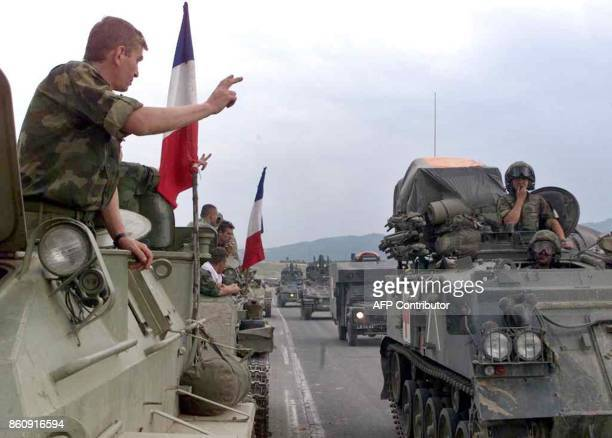 Serb soldiers flash the threefinger Serb salute 12 June 1999 as they drive during their withdrawal from Kosovo past KFOR troops arriving in Kacanik...