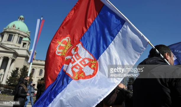 Serb ultranationalists wave the national flag on March 17 in Belgrade during a protest marking the ninth anniversary of riots that left 19 dead and...