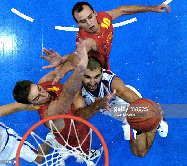 Serbia/Montenegros player Predrag Stojakovic tries to hit the basket while Spanish Pau Gasol and Carlos Jimnenez try to stop him, during their Group...