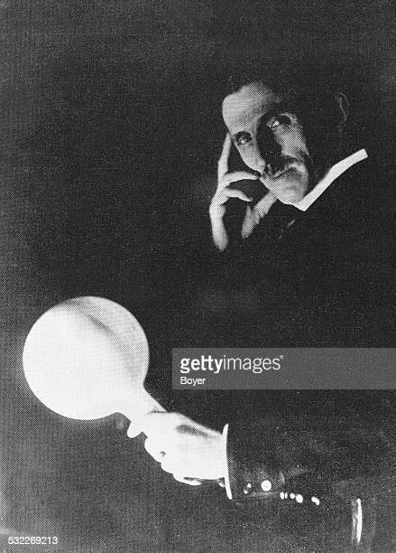 Serbian American inventor and electrical engineer Nikola Tesla demonstrates the safety of AC electrical current by allowing it to pass through his...