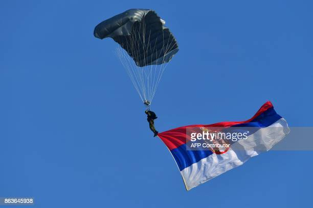 A Serbian Army paratrooper displays the Serbian national flag during a ceremony at Batajnica military airport near Belgrade on October 20 2017 Russia...