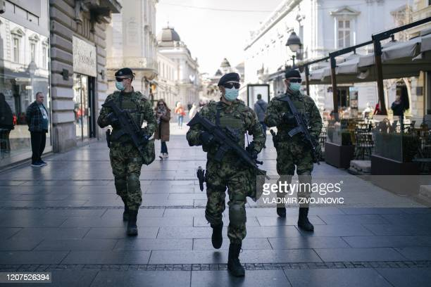 Serbian army soldiers wearing gloves and face masks as preventive measures against COVID-19 , patrol on one of the main pedestrian streets in...