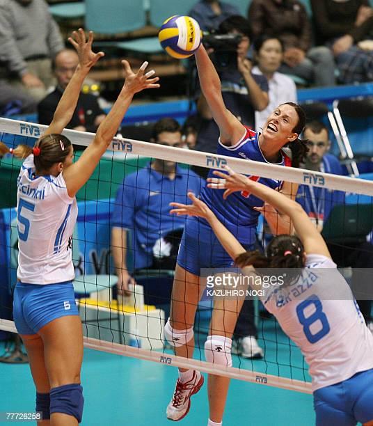 Serbian attacker Jelena Nikolic spikes the ball over Italian blockers Francesca Piccinini and Jenny Barazza during their second round match at the...