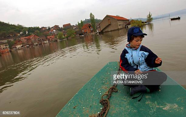 Serbian boy rides in a canoe through flood waters of Danube River in the village of Ritopek near Belgrade, 21 April 2006. After reaching new record...