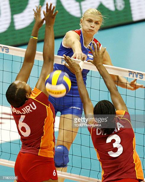 Serbian captain Vesna Citakovic spikes the ball through the block of Kenyan Catherine Wanjiru and Diana Khisa during the third round match against...