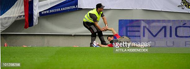 A Serbian fan is dragged out the pitch by a local security member during a friendly football match between Serbia and NewZealand in the Hypo Arena...