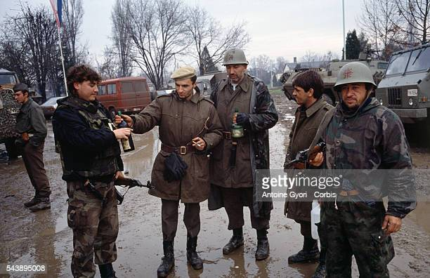 Serbian fighters drink wine and smoke cigarettes among the ruins of Vukovar after a threemonth battle between the Croatian armed forces and the...