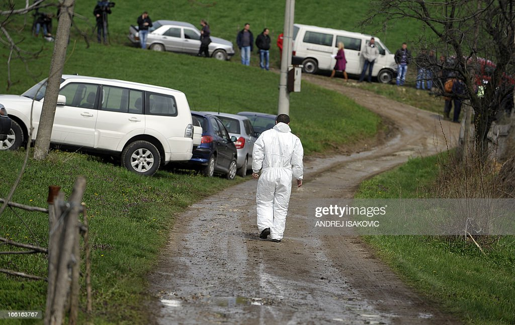 A Serbian forensic expert walks toward the site where a man shot dead 13 relatives and neighbours, including a two-year-old child, in the village of Velika Ivanca, 40 kilometres south of capital Belgrade, on April 9, 2013.