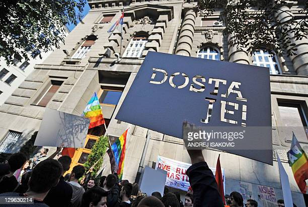 """Serbian gay activists display a banner which translates as """"It's Enough!"""" during a protest front of the Serbian government building in Belgrade on..."""