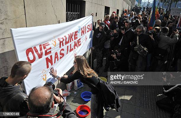 """Serbian gay activists display on October 19, 2011 a banner, reading: """"These arms are not violent,"""" during a protest front of Serbian government..."""