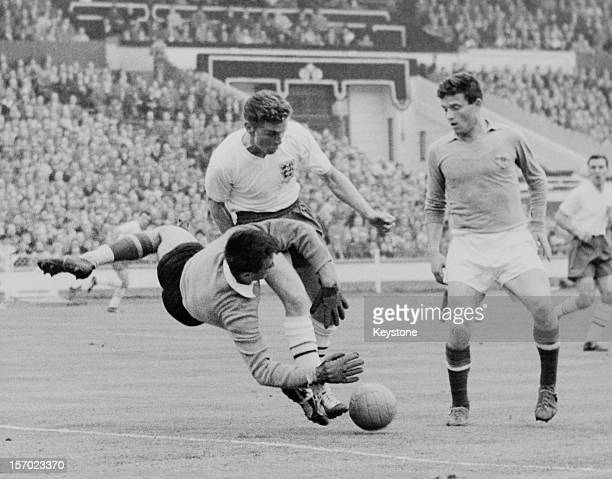 Serbian goalkeeper Milutin Soskic of Yugoslavia stops an attack by Joe Baker of England during an international match at Wembley Stadium London 11th...