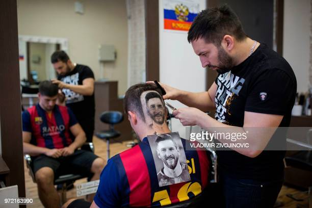TOPSHOT Serbian hairdresser Mario Hvala creates a hair tattoo showing the portrait of Argentinian football player Lionel Messi on the head of a...