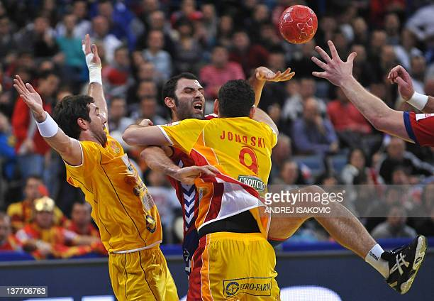 Serbian Ivan Stankovic vies with Macedonian Filip Mirkulovski and Ace Jonovski during their Men's EHF Euro 2012 Handball Championship match Serbia vs...
