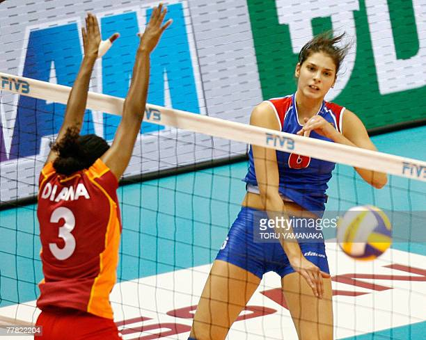 Serbian Jovana Brakocevic spikes the ball through the block of Kenyan Diana Khisa and Jane Wacu during the third round match against Poland in the...