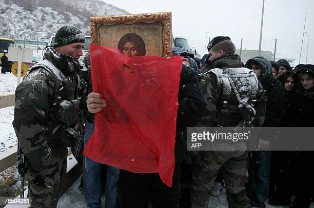 A Serbian man carries an icon 15 December 2007 as French KFOR soldiers check believers in front of rebuilt Serbian Orthodox monastery of St Joanikije...