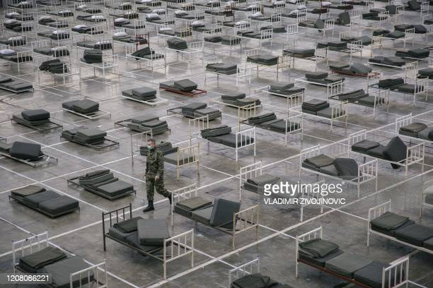 Serbian military personal wearing a protective mask walks amongst beds set up inside a hall at the Belgrade Fair to accommodate people suffering from...