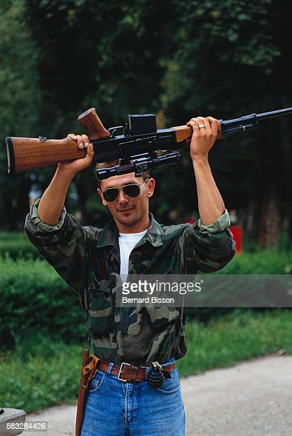 A Serbian militiaman holds a rifle above his head following conflicts in Glina on July 31 1991