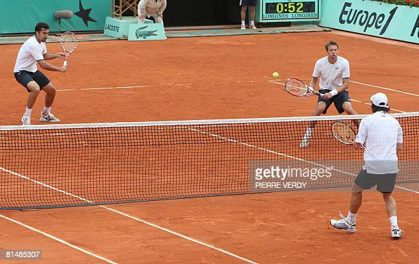Serbian Nenad Zimonjic hits a return to Uruguayan player Pablo Cuevas and Peruvian Luis Horna next to his teammate Canadian Daniel Nestor during...