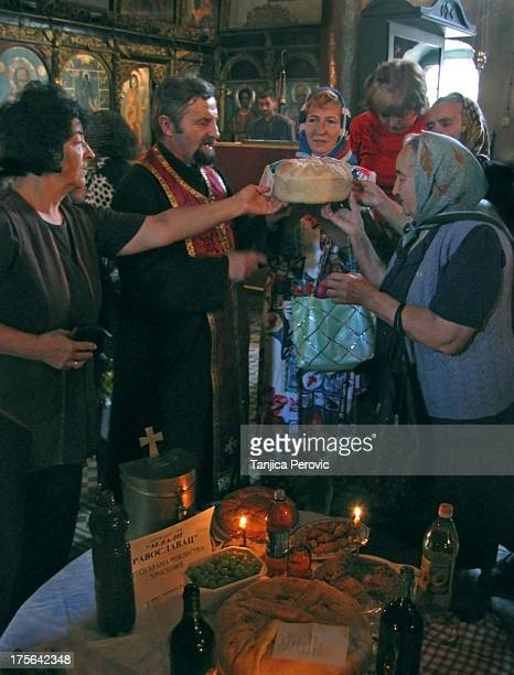 Serbian Orthodox Christian priest and some faithful women during rite of Serbian Slava holding Slava bread and rotating it while chanting feast hymns...