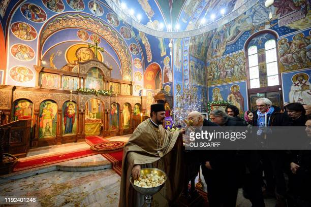 Serbian Orthodox Christian priest Father Nenad Popovic gives communion to worshippers during a service of the Nativity of Christ Liturgy at the...