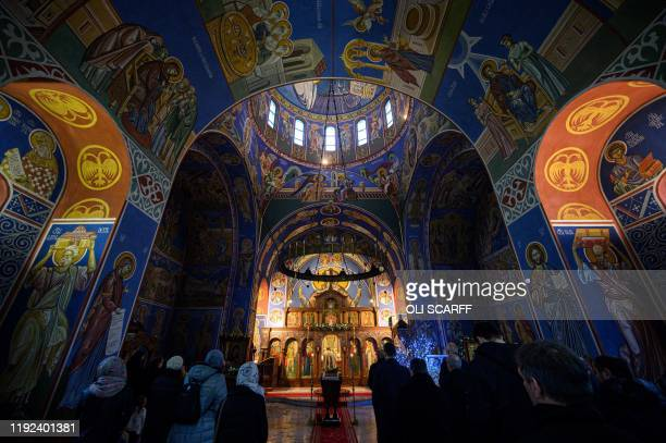 TOPSHOT Serbian Orthodox Christian priest Father Nenad Popovic leads worshippers during a service of the Nativity of Christ Liturgy at the Serbian...