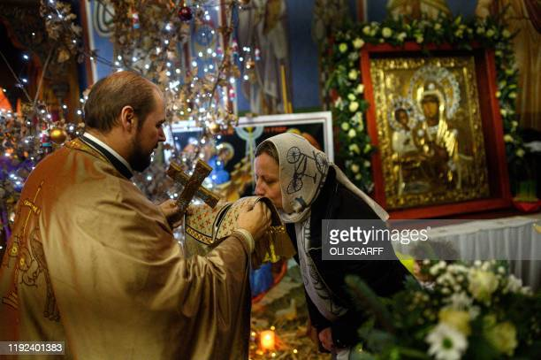 Serbian Orthodox Christian priest Father Nenad Popovic offers confession to worshippers during a service of the Nativity of Christ Liturgy at the...