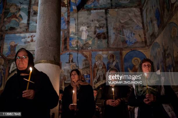 Serbian Orthodox Christians hold candles as they take part in a midnight Easter service at Sukovo Monastery in Sukovo near the town of Pirot early on...