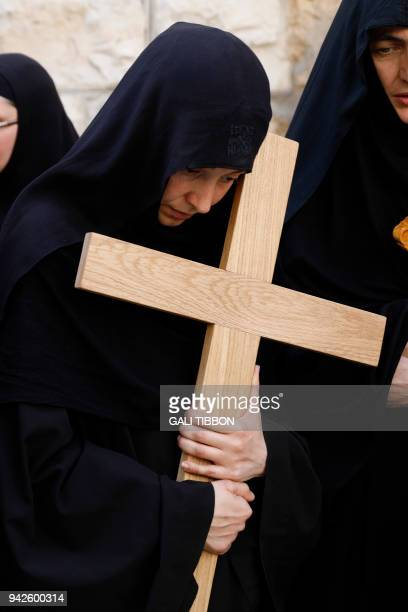 Serbian Orthodox nuns carry wooden crosses along the Via Dolorosa during the Orthodox Good Friday procession in Jerusalem's Old City on April 6 2018...