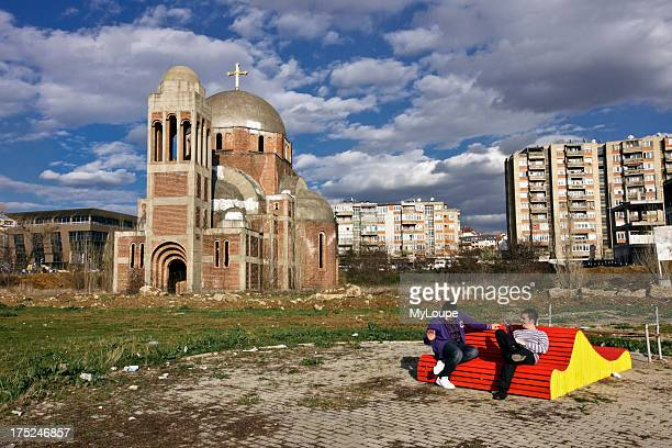 Serbian Orthodox Temple of Saint Saviour built in 1998 and unfinished because of the war. Two university students sitting on a bench at Pristina...