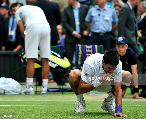 Serbian player Novak Djokovic eats the grass after beating Spanish player Rafael in the men's single final at the Wimbledon Tennis Championships at...