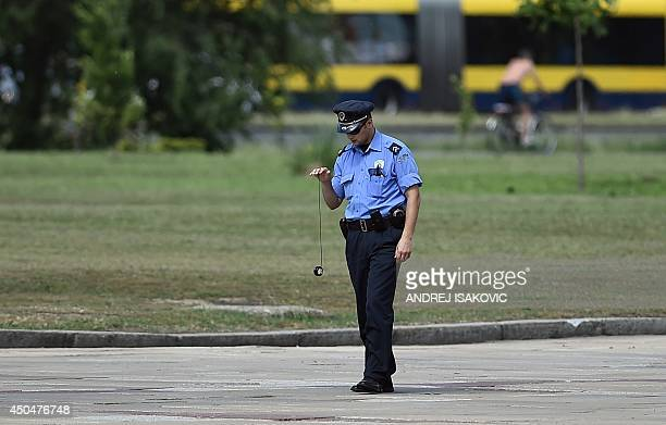 A Serbian police officer plays with a yoyo ahead of the arrival of the Belorussian president for a meeting with his Serbian counterpart in Belgrade...