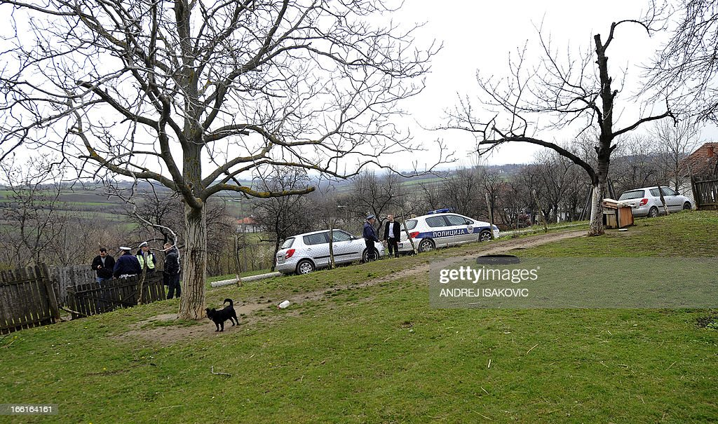 Serbian police officers guard the entrance to a yard in the village of Velika Ivanca, 40 kilometres south of capital Belgrade, on April 9, 2013, where a man shot dead 13 relatives and neighbours, including a two-year-old child, in the country's worst killing spree in two decades.