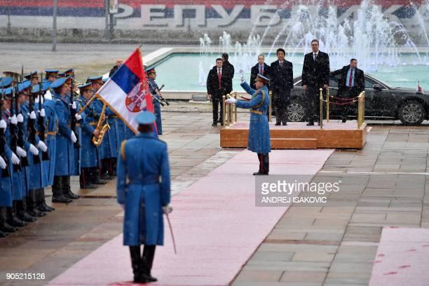 Serbian President Aleksandar Vucic and Japanese Prime Minister Shinzo Abe review a guard of honour as snow falls prior their meeting in Belgrade on...