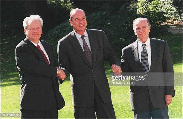 Serbian President Slobodan Milosevic and Bosnian President Alija Izetbegovic shake hands with French President Jacques Chirac 03 October 1996 in the...