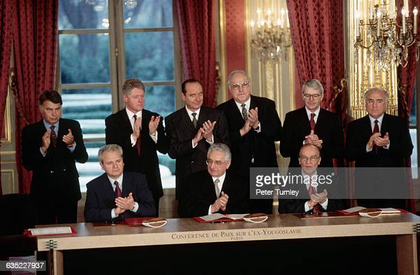 Serbian President Slobodan Milosevic Croat President Franjo Tudjman and Bosnian President Alija Izetbegovic sit in front of their copies of the...