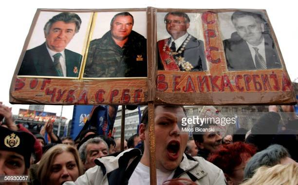 Serbian Radical party supporter holds photos of war crimes suspects Radovan Karadzic Ratko Mladic and Vojislav Seselj at a rally in Belgrade February...